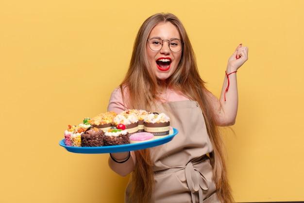 Jonge mooie vrouw. een triomf vieren als een winnaarbakker met cupcakes