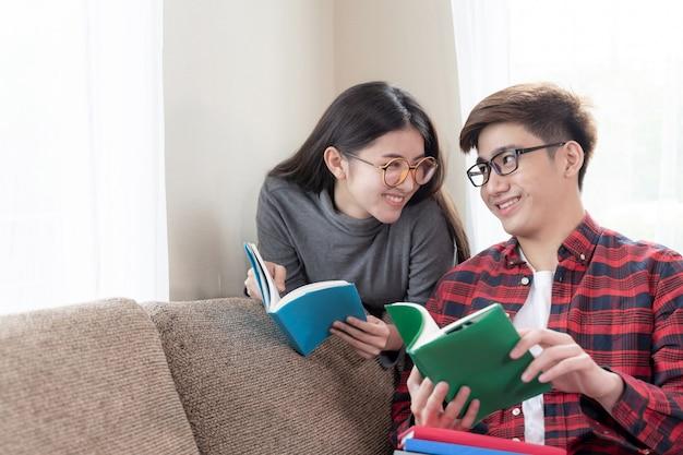 Jonge mooie vrouw en knappe vriendje dragen van een bril en zitten aan het lezen van boeken op bank thuis