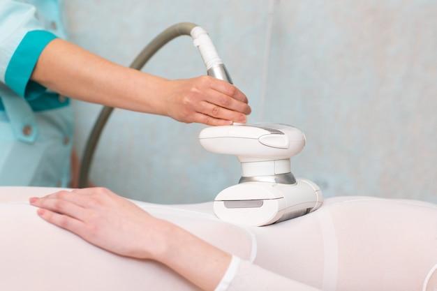 Jonge mooie vrouw en lpg-massageprocedure in kuuroordkliniek