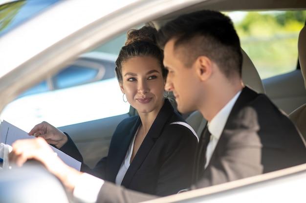 Jonge mooie vrouw en man in pakken in auto