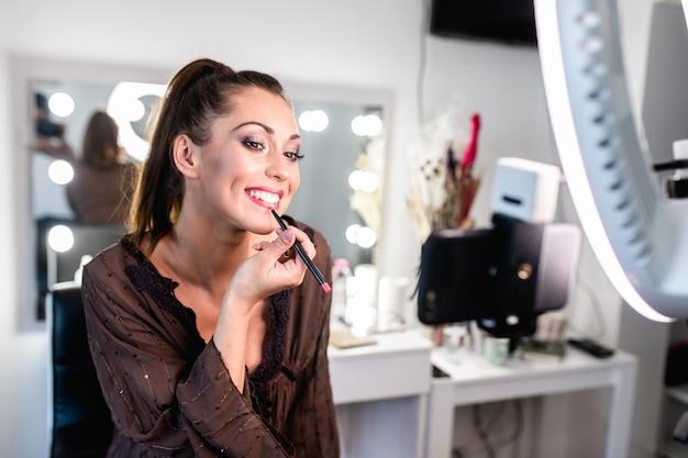 Jonge mooie vrouw en professionele beauty make-up artiest vlogger of blogger die make-up tutorial opneemt om te delen op website of sociale media.