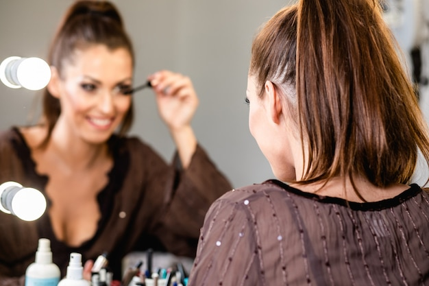 Jonge mooie vrouw en professionele schoonheidsmake-upartiest vlogger die make-uphandleiding opneemt om te delen op website of sociale media