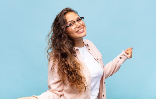 Jonge mooie vrouw gebaren op blauwe muur