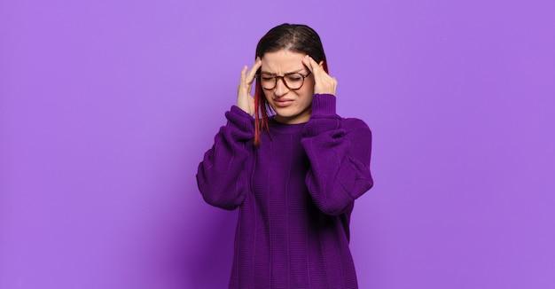 Jonge mooie vrouw gebaren op gekleurde muur
