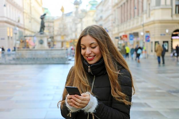 Jonge mooie vrouw, gekleed in casual winterkleren met behulp van telefoon buiten in europese stad. meisje met mobiele telefoon in hand in de hoofdstraat van wenen, oostenrijk.