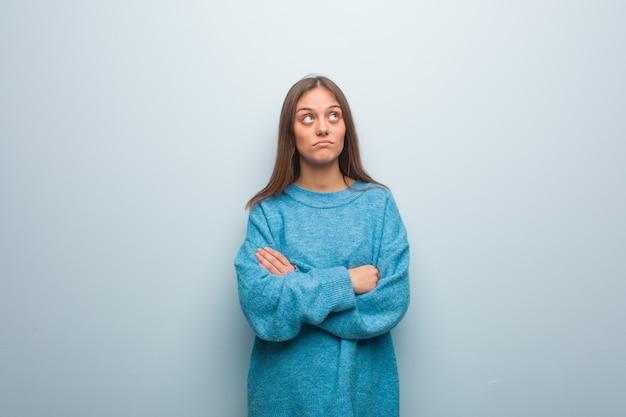 Jonge mooie vrouw, gekleed in een blauwe trui moe en verveeld