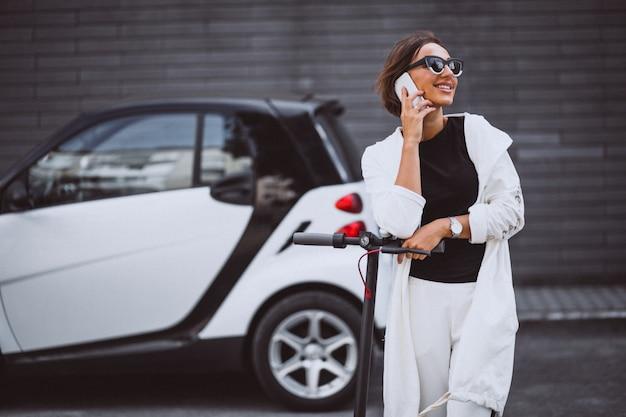 Jonge mooie vrouw gekleed in witte paardrijden scooter
