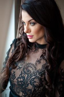 Jonge mooie vrouw, gekleed in zwarte avondjurk poseren voor valentijn daten
