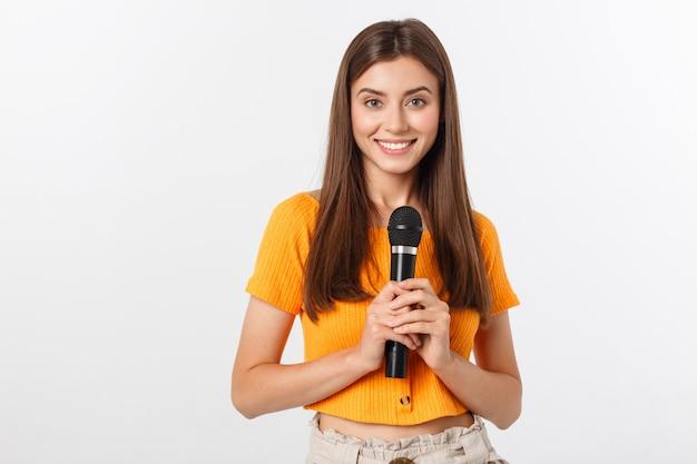 Jonge mooie vrouw gelukkig en gemotiveerd, zingt een lied met een microfoon, presenteert een evenement of heeft een feest, geniet van het moment