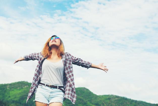 Jonge mooie vrouw genieten van de vrijheid en het leven in de natuur achter