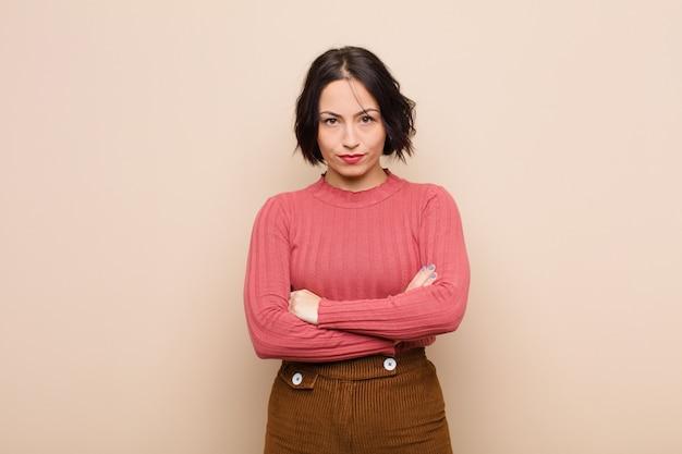 Jonge mooie vrouw gevoel ontstemd en teleurgesteld, op zoek ernstig, geërgerd en boos met gekruiste armen tegen beige muur