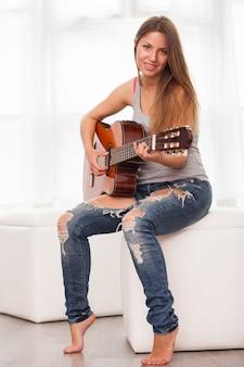 Jonge mooie vrouw gitaarspelen