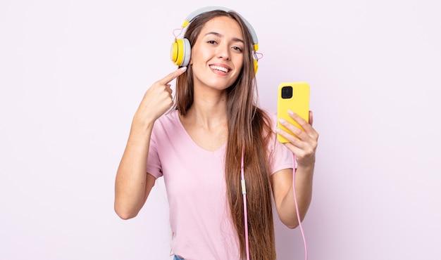Jonge mooie vrouw glimlachend vol vertrouwen wijzend naar eigen brede glimlach. koptelefoon en smartphone