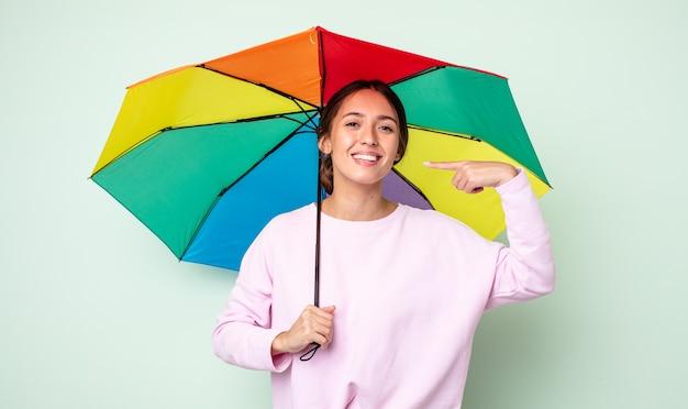 Jonge mooie vrouw glimlachend vol vertrouwen wijzend naar eigen brede glimlach. paraplu concept