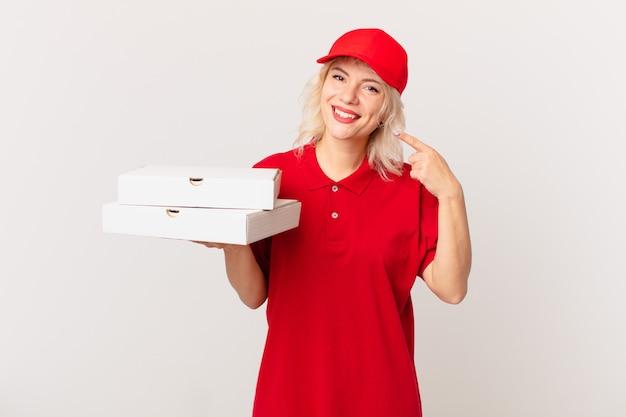Jonge mooie vrouw glimlachend vol vertrouwen wijzend naar eigen brede glimlach. pizza bezorgconcept