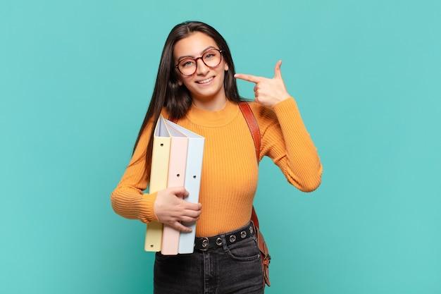 Jonge mooie vrouw glimlachend vol vertrouwen wijzend naar eigen brede glimlach, positieve, ontspannen, tevreden houding. studentenconcept