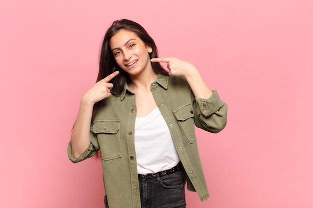 Jonge mooie vrouw glimlachend vol vertrouwen wijzend op eigen brede glimlach, positieve, ontspannen, tevreden houding Premium Foto