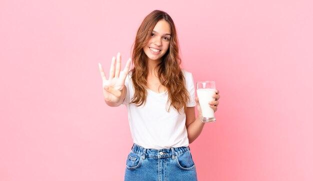Jonge mooie vrouw glimlacht en ziet er vriendelijk uit, toont nummer vier en houdt een glas melk vast