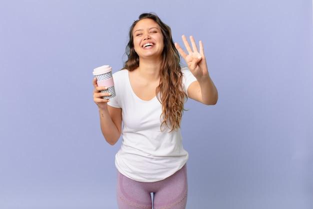 Jonge mooie vrouw glimlacht en ziet er vriendelijk uit, toont nummer vier en houdt een kopje koffie vast