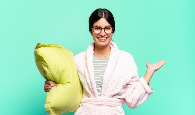 Jonge mooie vrouw glimlacht, voelt zich zelfverzekerd, succesvol en gelukkig, toont concept of idee op kopieerruimte aan de zijkant