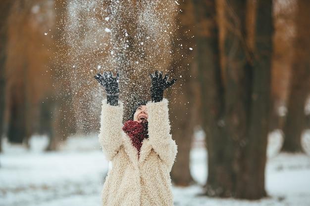Jonge mooie vrouw gooit sneeuw boven het hoofd