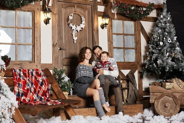 Jonge mooie vrouw, haar knappe echtgenoot en hun schattige zoontje poseren op de trappen van het versierde huis voor kerstmis