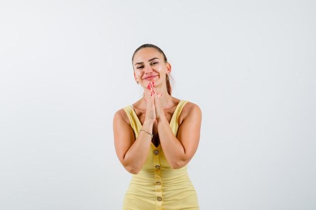 Jonge mooie vrouw hand in hand in gebed gebaar in jurk en op zoek dankbaar, vooraanzicht.