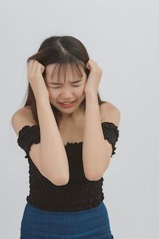 Jonge mooie vrouw heeft hoofdpijn op grijs; portret van aziatisch bedrijfs ernstig wijfje of droevige migraine, gezondheidszorg en zaken.