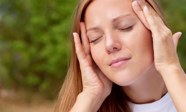 Jonge mooie vrouw heeft hoofdpijn
