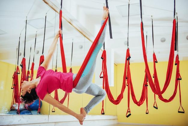 Jonge mooie vrouw het beoefenen van yoga fly met een hangmat in de studio.