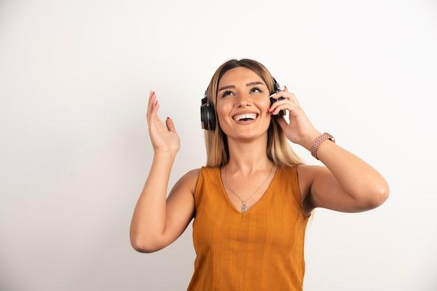 Jonge mooie vrouw hoofdtelefoon dragen op witte achtergrond.
