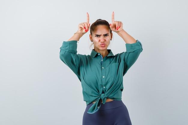 Jonge mooie vrouw houdt handen boven het hoofd als hoorns met pruilende lippen in groen shirt en ziet er attent uit. vooraanzicht.