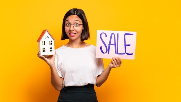 Jonge mooie vrouw huis te koop concept