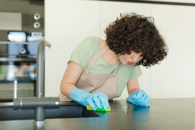 Jonge mooie vrouw huishoudster afwas thuis
