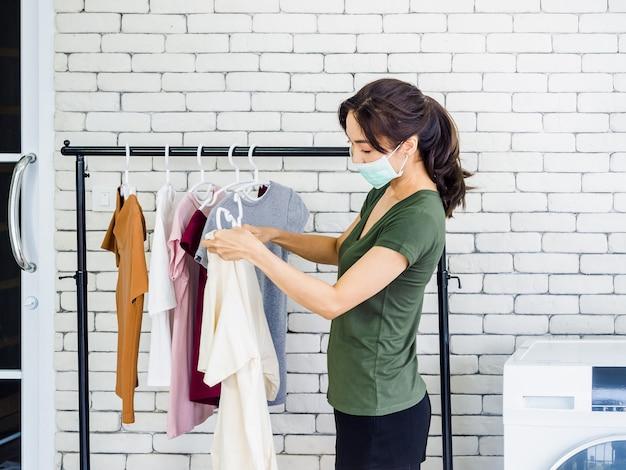 Jonge mooie vrouw, huisvrouw in casual dragen van beschermend gezichtsmasker opknoping droog shirt met hanger aan de waslijn na het wassen in de buurt van de wasmachine in de wasruimte op de witte muur.