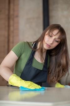 Jonge mooie vrouw huisvrouw in gele rubberen beschermende handschoenen en zwarte schort huis schoonmaken, wrijft stof, wastafel met behulp van microfiber doek. schoonmaakservice voor huishoudelijk werk, huishoudelijk concept