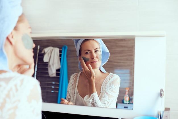Jonge mooie vrouw in badjas en met handdoek op hoofd die gezichtsmasker voor spiegel in badkamers verwijderen. huidverzorging en schoonheid concept