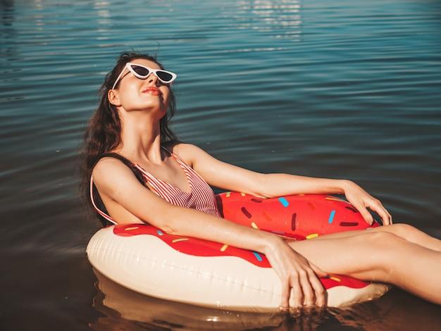 Jonge mooie vrouw in badkleding en zonnebril drijvend op de zee