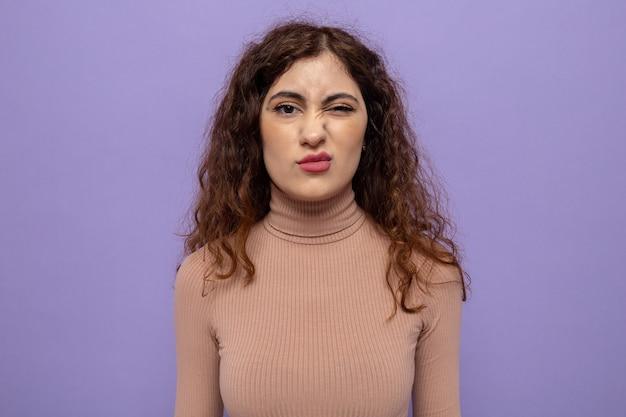 Jonge mooie vrouw in beige coltrui die een wrange mond maakt met een teleurgestelde uitdrukking die op paars staat