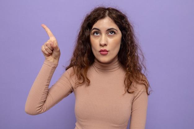 Jonge mooie vrouw in beige coltrui die opkijkt met een serieus gezicht wijzend met de wijsvinger naar de zijkant