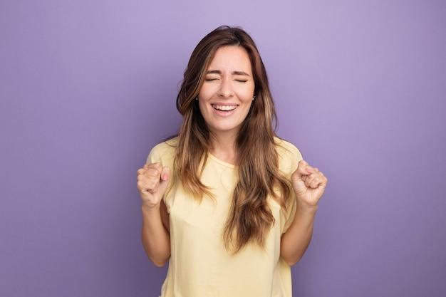 Jonge, mooie vrouw in beige t-shirt, blij en opgewonden, verheugd over haar succes en balde vuisten die over paars staan