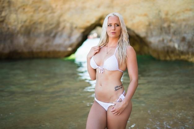 Jonge mooie vrouw in bikini op overzeese achtergrond
