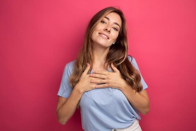 Jonge mooie vrouw in blauw t-shirt hand in hand op haar borst en voelt zich dankbaar glimlachend vriendelijk over roze achtergrond