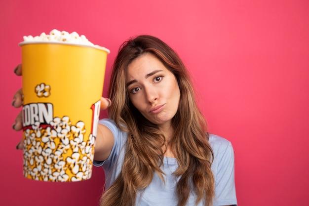 Jonge mooie vrouw in blauw t-shirt met emmer met popcorn die naar de camera kijkt