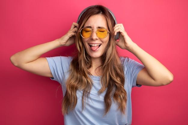 Jonge mooie vrouw in blauw t-shirt met gele bril