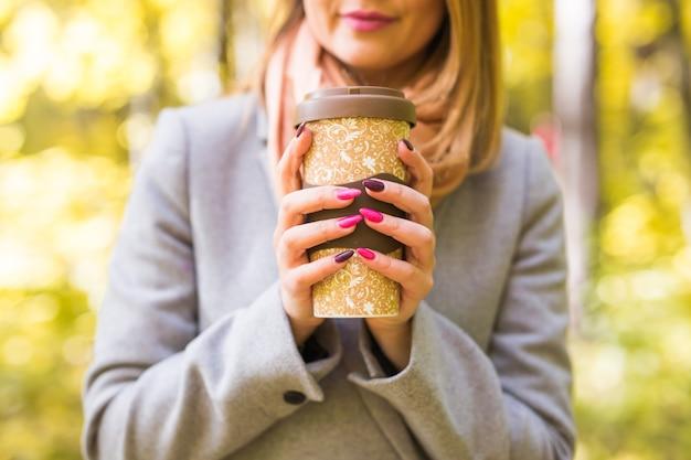 Jonge mooie vrouw in blauwe jas met een kopje koffie