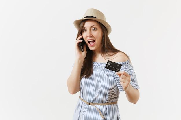Jonge mooie vrouw in blauwe jurk, hoed praten op mobiele telefoon, aangenaam gesprek voeren, creditcard houden geïsoleerd op een witte achtergrond. mensen, bankconcept. reclame gebied. ruimte kopiëren