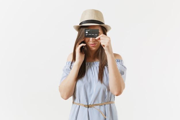 Jonge mooie vrouw in blauwe jurk, hoed praten op mobiele telefoon, vasthouden, verbergen, bedekken ogen of gezicht met creditcard geïsoleerd op een witte achtergrond. mensen, bankconcept. reclame gebied. ruimte kopiëren