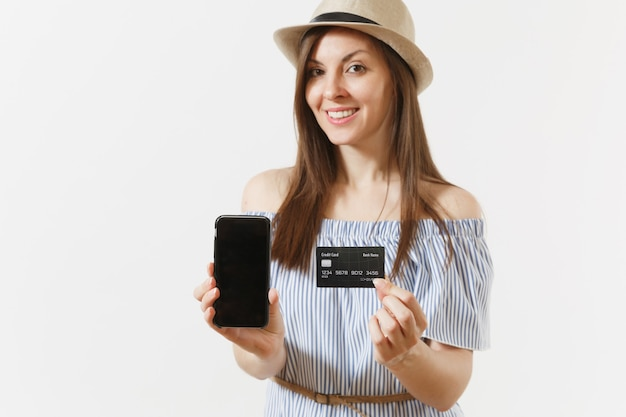 Jonge mooie vrouw in blauwe jurk, hoed weergegeven: camera mobiele telefoon met leeg zwart leeg scherm, met creditcard geïsoleerd op een witte achtergrond. mensen, bankconcept. reclame gebied. ruimte kopiëren