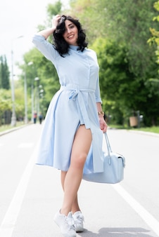 Jonge mooie vrouw in blauwe jurk poseren